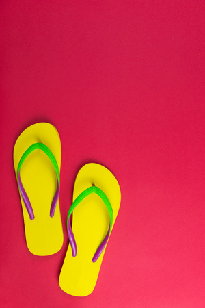 Pair of yellow flip flop on red background