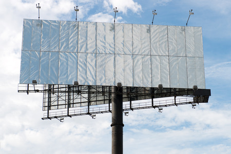 Blank large billboard against cloudy blue sky photo