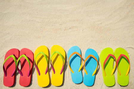 Four pairs of beach sandals on white sand photo