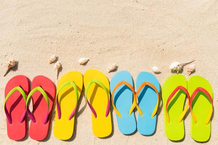 Cuatro pares de sandalias en una fila en la playa Foto de archivo