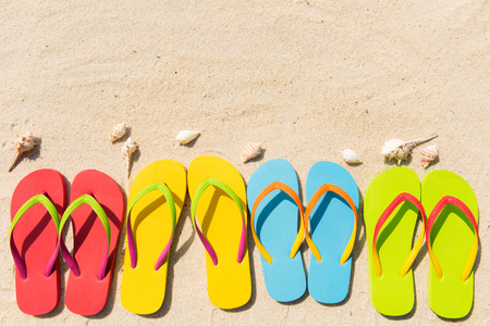 flip flops on the beach: Four pairs of flip flops in a row on beach