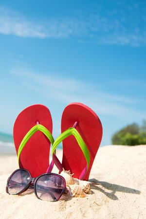 Rode flip flop en een zonnebril op het strand tegen de heldere blauwe hemel