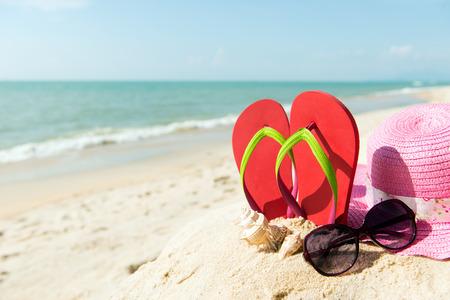 Flip flop rojo con gafas de sol y sombrero de ala ancha de color rosa en la playa Foto de archivo