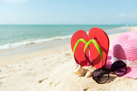 Red flip flop with sunglasses and pink floppy hat on beach Stockfoto