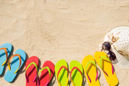flipflops: Row of colorful flip flops, sunglasses, floppy hat on beach Stock Photo