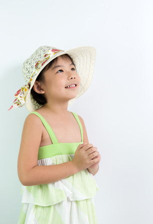 hoping: Portrait of little Asian girl with summer hat looking up