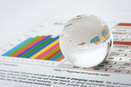Glass world globe rest on financial sheet Stock Photo - 27550211