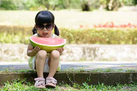 Little child with sunglasses and big slice of watermelon sitting in the park photo