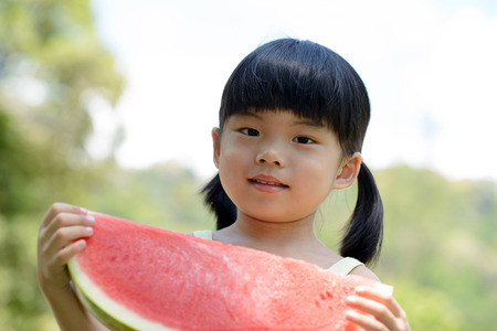Asian child with big slice of watermelon photo