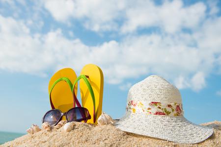 Yellow flip flop, sunglasses and floppy hat at the beach 版權商用圖片