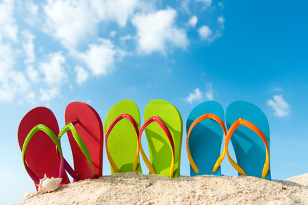 Row of colorful flip flops on beach against sunny sky Stock Photo