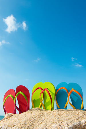 thongs: Row of colorful flip flops on beach against sunny sky Stock Photo