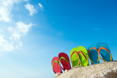 flip: Row of colorful flip flops on beach against sunny sky Stock Photo