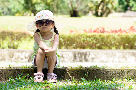 spring time: Little Asian girl wear sunglasses and floppy hat sitting in the park