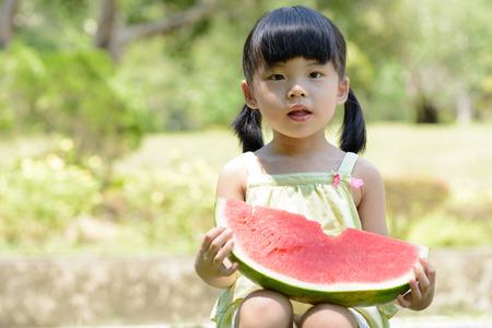 niños chinos: La sandía pequeña bebé asiática comer en el parque