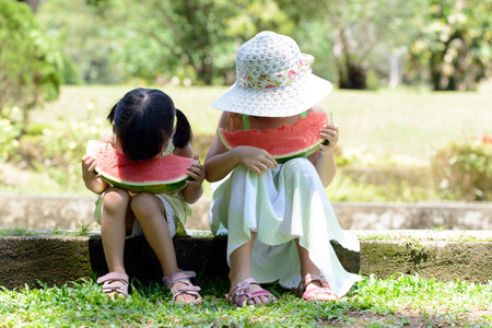 Two sister kids eating watermelon in the park photo