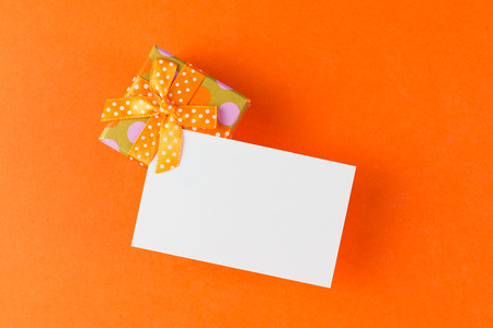 wrapped present: Gift box with blank card over orange background