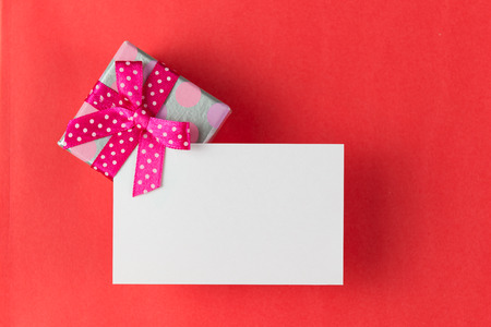 Gift box with blank card over red background