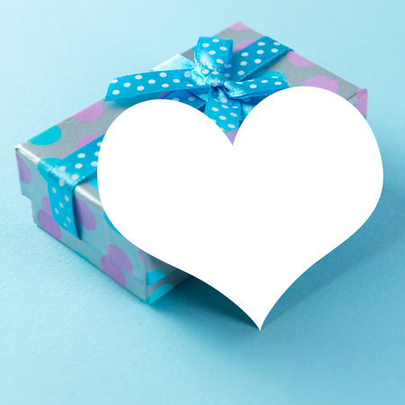 heart shaped box: Blue gift box with heart shaped plain card over blue background