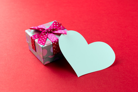 blessing: Red gift box with heart shaped plain card over red background Stock Photo