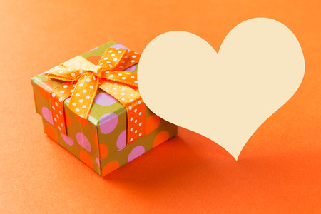 blessing: Orange gift box with heart shaped plain card over orange background