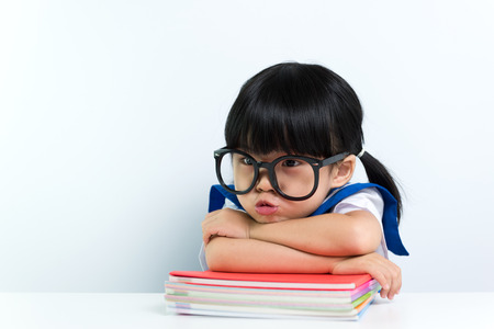 smart girl: Little Asian girl wearing eyeglasses with books