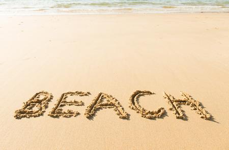 Word beach written on the yellow sandy beach photo