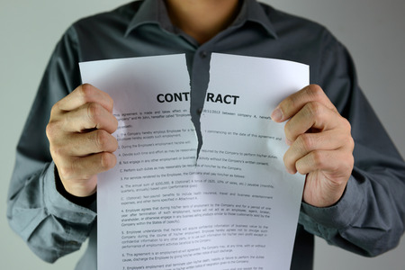 Businessman ripping a contract down to the centre