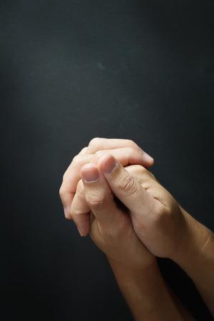 Close up of praying hand on black background