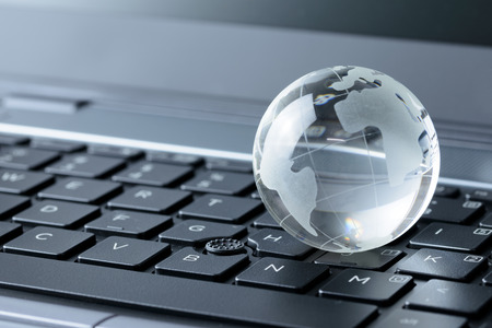 Close up of glass globe on laptop keyboard Stock Photo