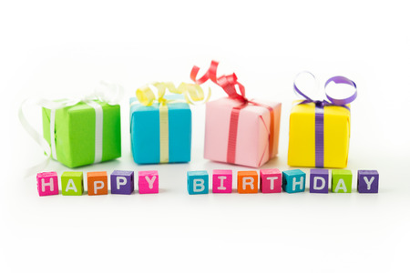 Colourful happy birthday message and gift boxes on white background photo