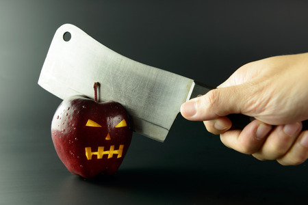 anger abstract: Cutting evil apple with knife on black background