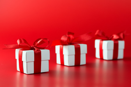 three gift boxes: Three white gift boxes with ribbons on red background