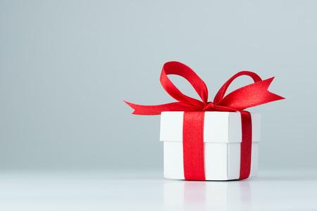 Caja de regalo con cinta roja sobre fondo blanco