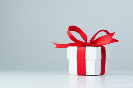christmas bonus: Gift box with red ribbon on white background