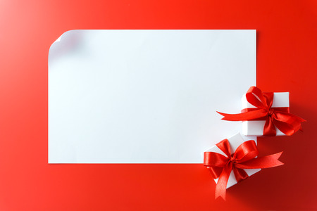 Gift boxes with blank card on red background photo