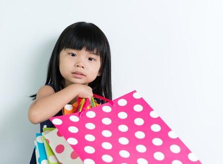 Little Asian girl holding shopping bags on white background photo