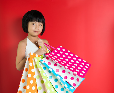 christmas promotion: Little Asian girl holding shopping bags on red background