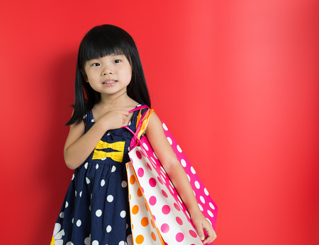 Little Asian girl holding shopping bags on red background photo