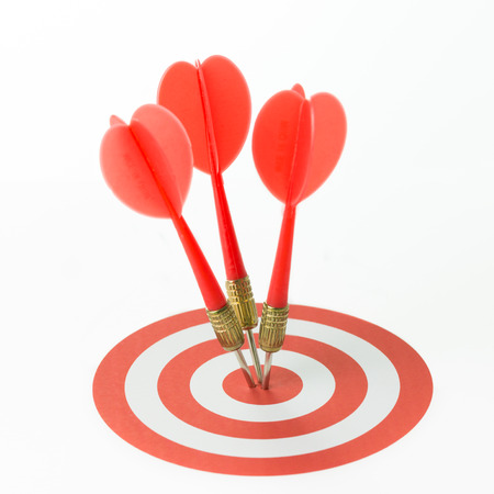Three red darts pinned right on the center of target Reklamní fotografie - 32406538