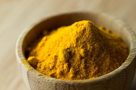 Close up of turmeric powder in wooden bowl Foto de archivo