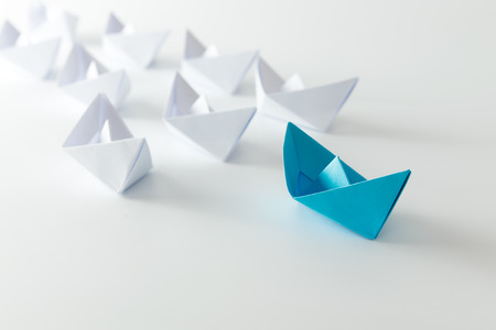 business leadership: Leadership concept using blue paper ship among white Stock Photo