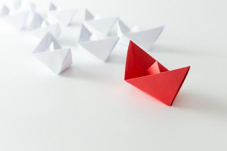 leader: Concepto de la direcci�n utilizando la nave de papel rojo entre los blancos Foto de archivo