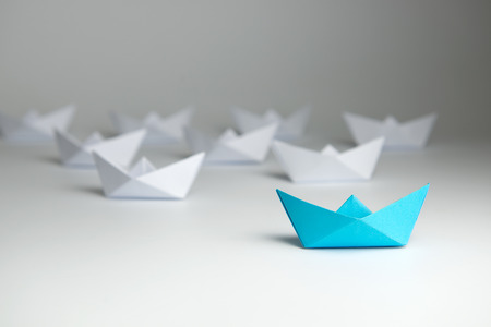 follow the leader: Leadership concept using blue paper ship among white Stock Photo