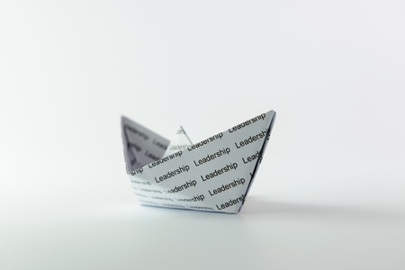 Close up of origami boat full of the word leadership photo