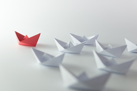 Leadership concept using red paper ship among white