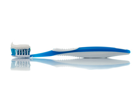 Blue toothbrush with toothpaste on white background