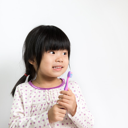 Little Asian girl in pyjamas holding toothbrush photo