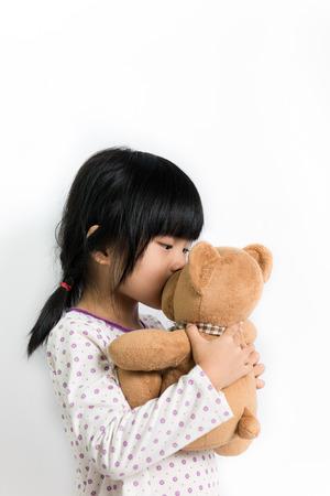 Little Asian girl in pyjamas kissing teddy bear