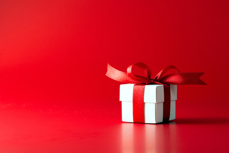 White gift box with ribbon on red background Foto de archivo